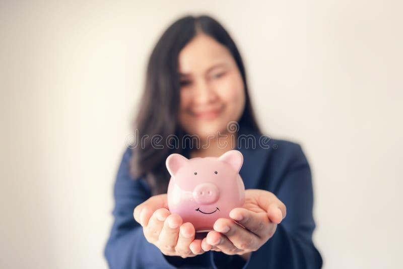 Nära övre stående av affärskvinnan Holding Piggy Bank på hennes händer, asiatisk affärskvinna i den enhetliga dräkten som visar s arkivfoto
