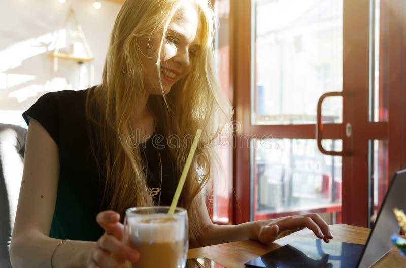 Nära övre stående av att le den europeiska blond-haired kvinnan med bärbara datorn royaltyfria bilder