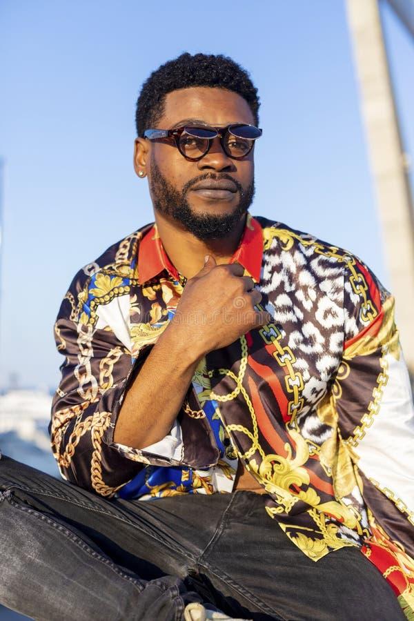 Nära övre stående av bärande solglasögon för en ung svart skäggig man som sitter, medan se kameran i kall inställning i e fotografering för bildbyråer