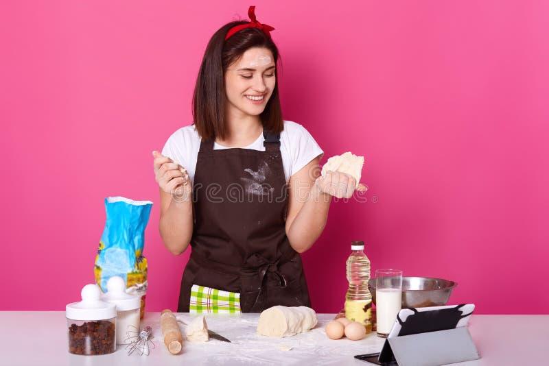 Nära övre stående av bagaren i förklädet som förbereder det välfyllda bagerit för pajer, hemmafru som förbereder sig fö royaltyfria bilder