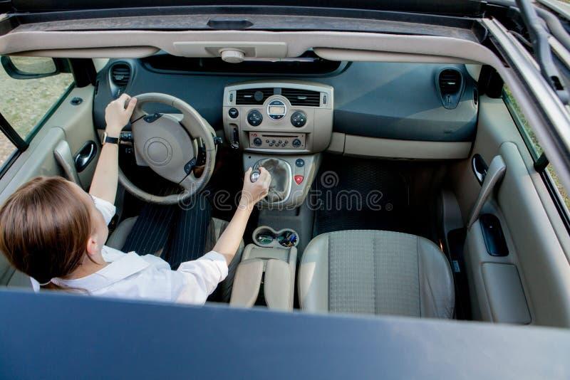 Nära övre stående av den angenäma seende kvinnlign med glat positivt uttryck, tillfredsställas med den oförglömliga bilresan, royaltyfri bild