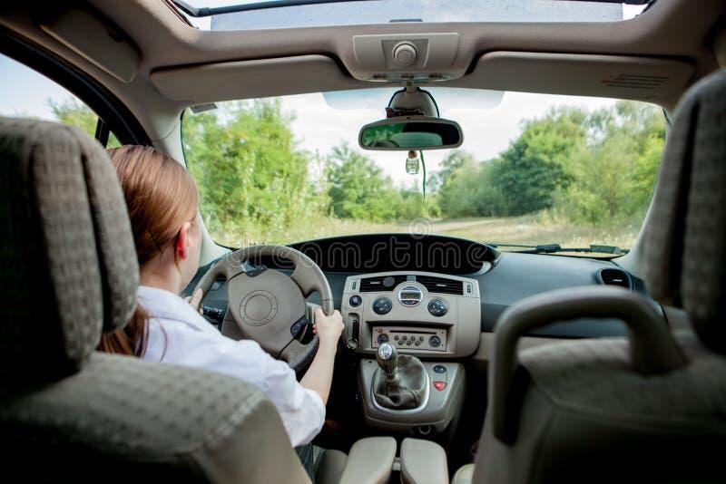 Nära övre stående av den angenäma seende kvinnlign med glat positivt uttryck, tillfredsställas med den oförglömliga bilresan, royaltyfri fotografi