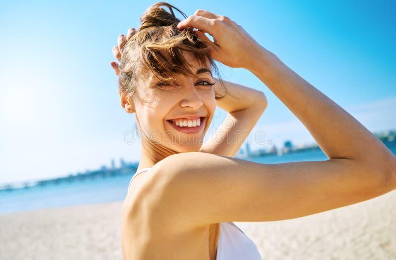 Nära övre stående av den härliga sexiga lyckliga kvinnan på sandstadsstranden med havsbakgrund Sommartidbegrepp royaltyfri foto