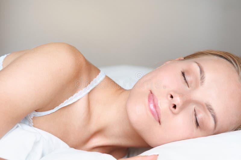 Nära övre stående av den härliga unga blonda kvinnan som sover i en vit säng arkivbilder