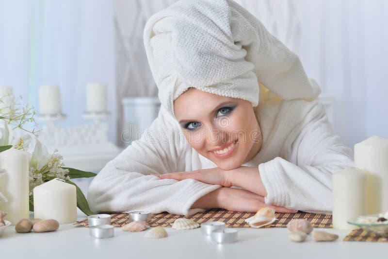 Nära övre stående av den härliga unga kvinnan med handduken på hennes huvud som lutar på tabellen arkivbild