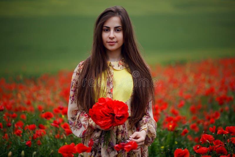 Nära övre stående av den långa unga kvinnan för hår med blommavallmo, innehav i händer en bukett av röda blommor royaltyfria bilder