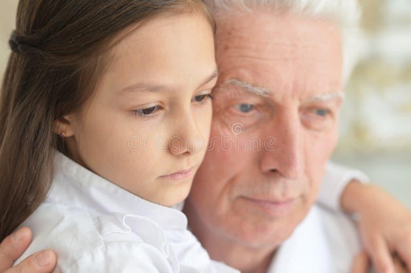 Nära övre stående av den ledsna farfadern och sondottern fotografering för bildbyråer