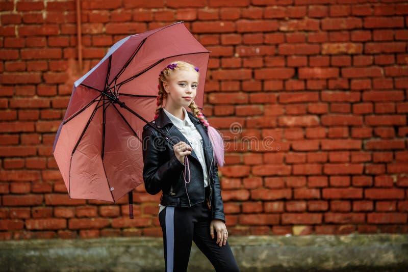 Nära övre stående av den lilla härliga stilfulla ungeflickan med ett paraply i regnet nära väggen för röd tegelsten som b arkivfoto