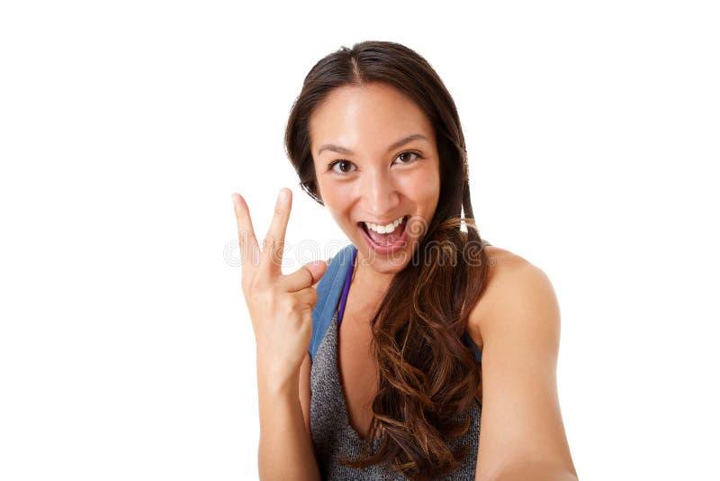 Nära övre stående av den lyckliga unga asiatiska kvinnan som tar selfie och gör fredtecknet med handen royaltyfria foton