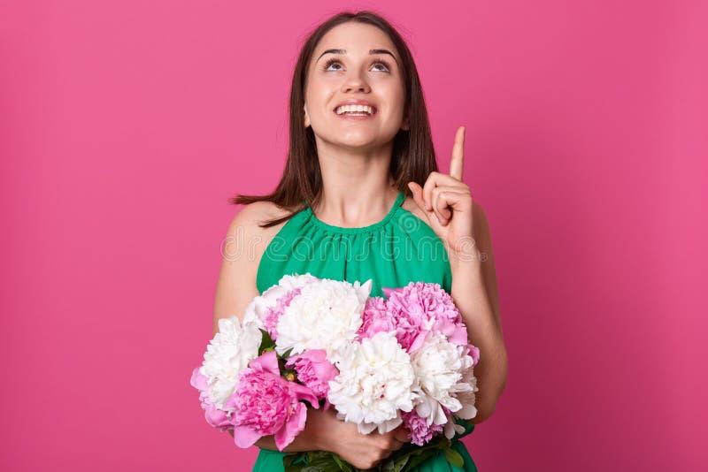 Nära övre stående av den mjuka positiva unga flickan som gör gesten, visningriktning och att se upp och att rymma hennes gåva och arkivfoto