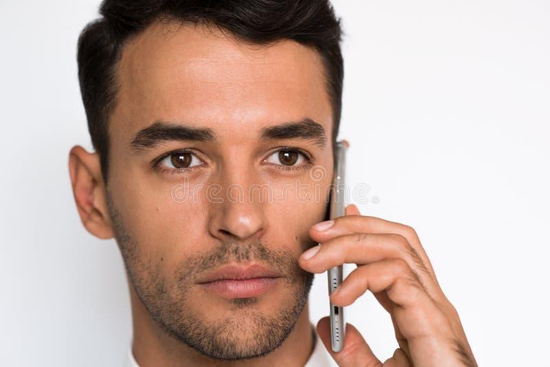 Nära övre stående av den stiliga unga mannen i den vita skjortan genom att använda mobiltelefonen som ser den en sidan med koncen arkivbild