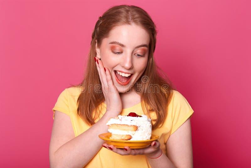 Nära övre stående av den tillfredsställda nöjda flickan med ljust - brunt hår, rymmer det enorma stycket av den smakliga kakan, h arkivbilder