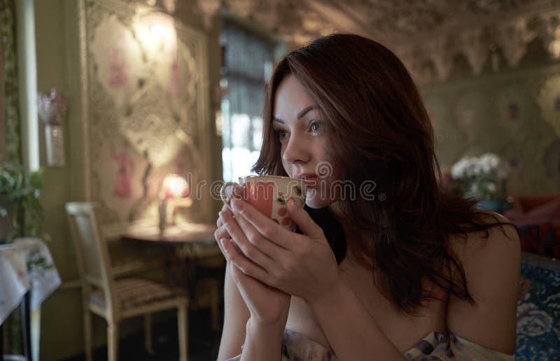 Nära övre stående av den unga kvinnan på kafét som dricker kaffe arkivbilder