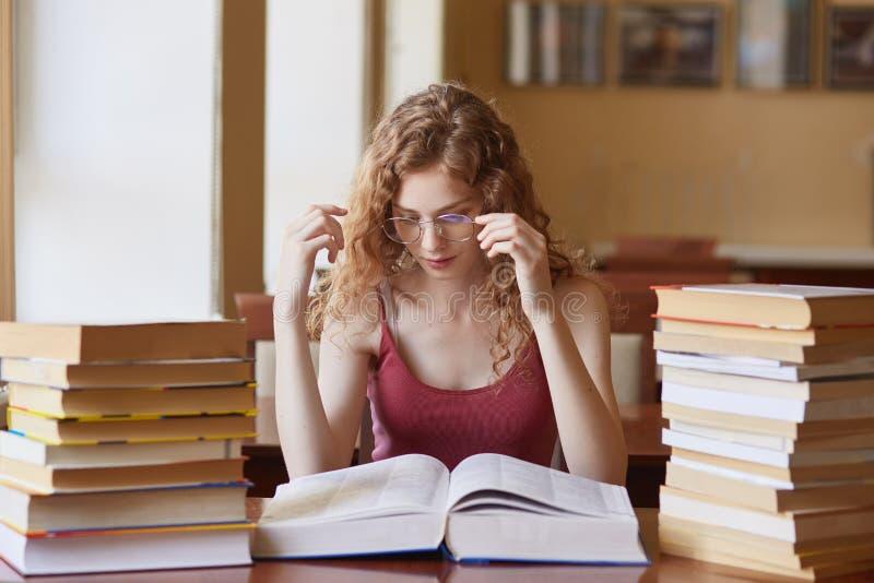 Nära övre stående av den unga kvinnan som trycker på hennes glasögon som läser pappersboken Kvinnlig student som spenderar lång t arkivbild