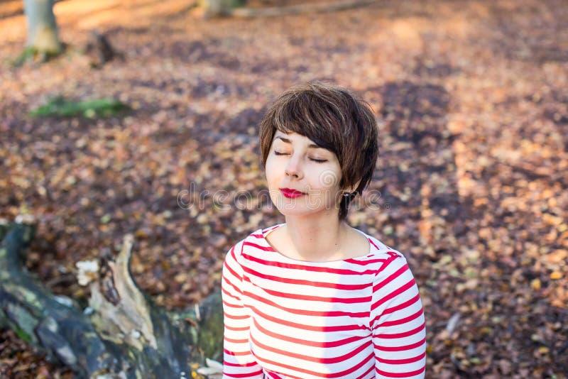 Nära övre stående av den unga le kvinnan med stängda ögon som sitter och kopplar av på det stupade trädet i höstlig skoghöst arkivbilder