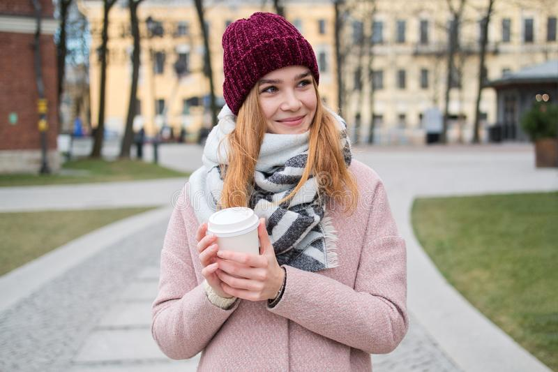Nära övre stående av den unga stilfulla blonda flickan i den röda hatten som rymmer den för avhämtning kaffekoppen royaltyfri foto