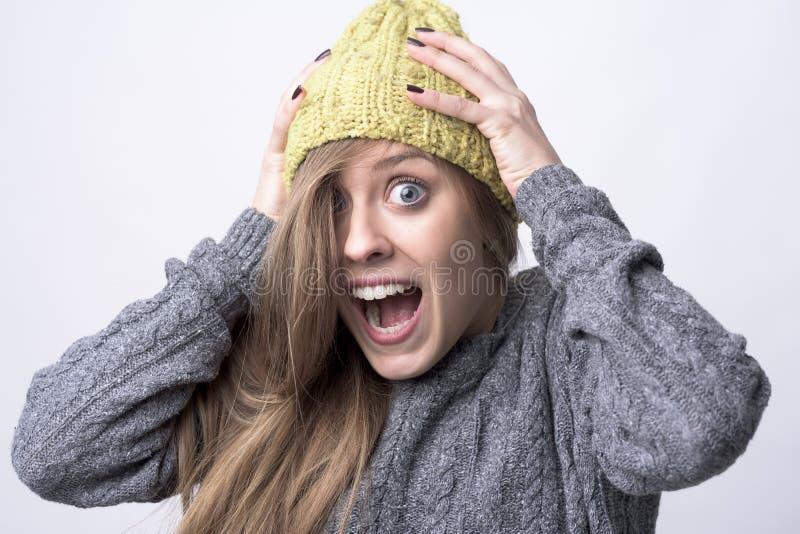 Nära övre stående av den uttrycksfulla unga kvinnan som skriker med händer på huvudet royaltyfri fotografi