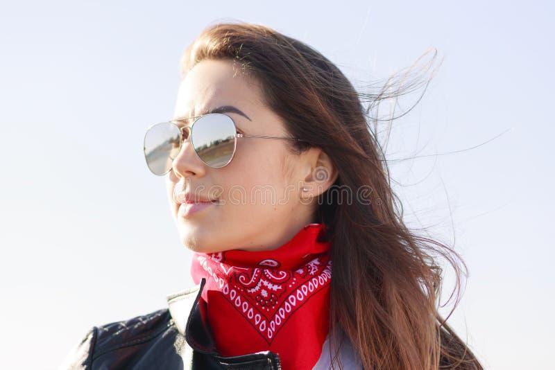 Nära övre stående av det bärande läderomslaget för härlig flicka, den röda bandanaen och kall solglasögon Posera för kvinnlig per arkivbilder