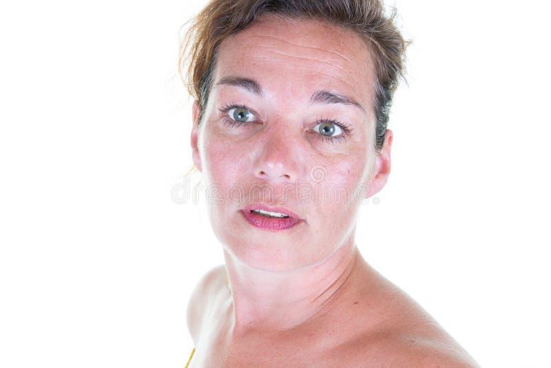 Nära övre stående av det härliga mellersta åldriga kvinnaanseendet vid den vita väggen royaltyfri fotografi