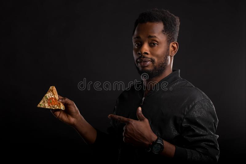 Nära övre stående av det unga afrikanska maninnehavstycket av pizza fotografering för bildbyråer