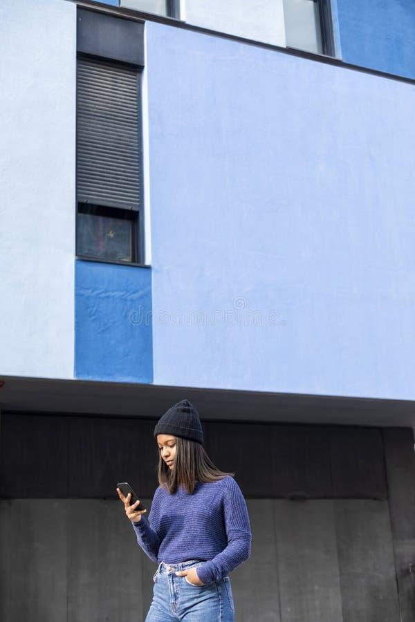 Nära övre stående av en härlig ung afrikankvinna som utomhus använder mobiltelefonen i staden arkivfoto