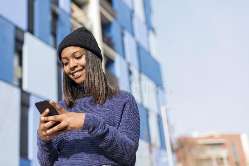 Nära övre stående av en härlig ung afrikankvinna som utomhus använder mobiltelefonen i staden royaltyfri foto