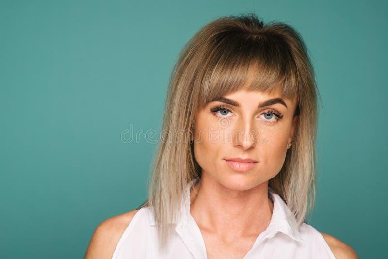 Nära övre stående av en härlig ung kvinna på blå bakgrund arkivfoto