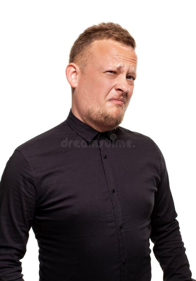 Nära övre stående av en säker, blond stilig ung man som bär den svarta skjortan som isoleras på vit bakgrund fotografering för bildbyråer