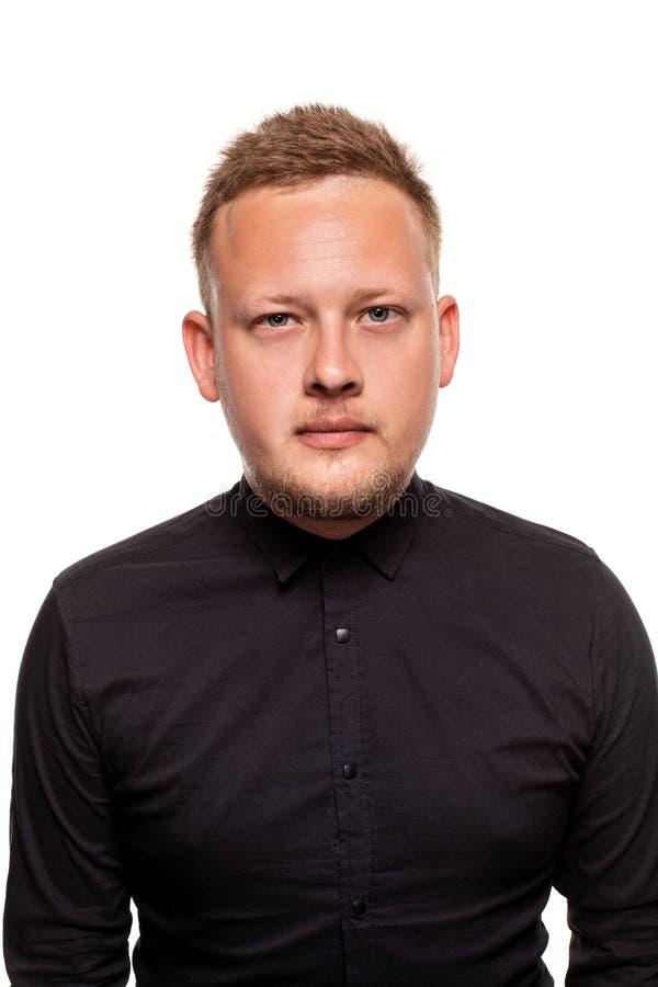 Nära övre stående av en säker, blond stilig ung man som bär den svarta skjortan som isoleras på vit bakgrund arkivbild
