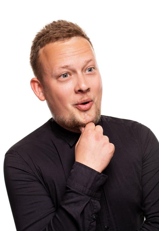 Nära övre stående av en säker, blond stilig ung man som bär den svarta skjortan som isoleras på vit bakgrund arkivfoto