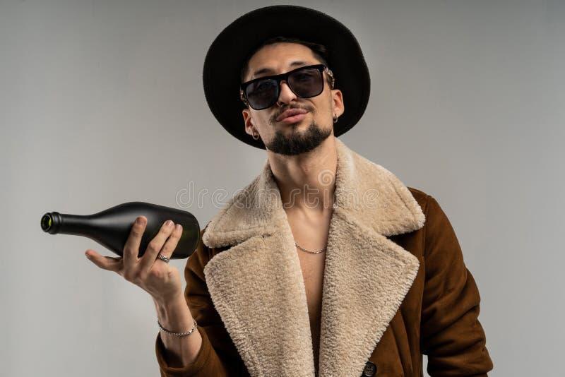 Nära övre stående av en skäggig hipsterman i solglasögon i ett brunt omslag och en svart hatt royaltyfria foton