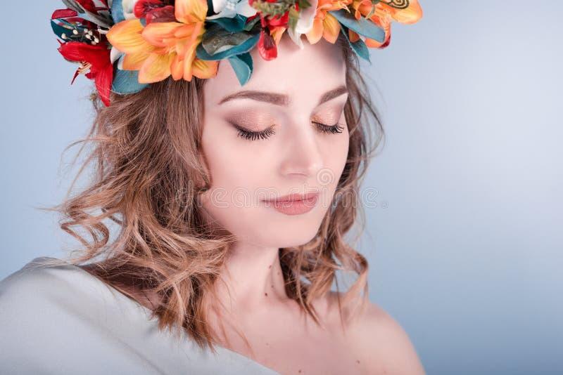 Nära övre stående av en ung kvinna för sinnlig vår i en krans av blommor Skönhet skönhetsmedel Smink arkivbild