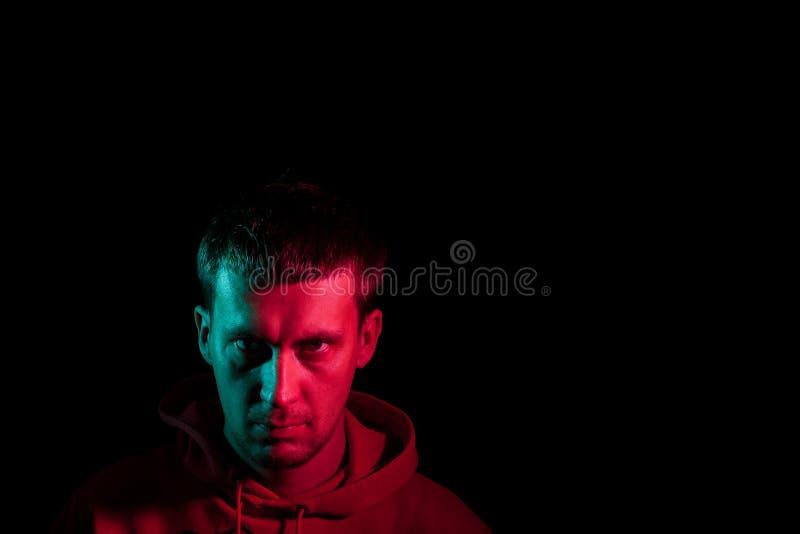 Nära övre stående av framsidan av en vuxen allvarlig manblick frowningly: rak näsa, uttrycksfulla ögon, öron, skägg; upplyst arkivfoto