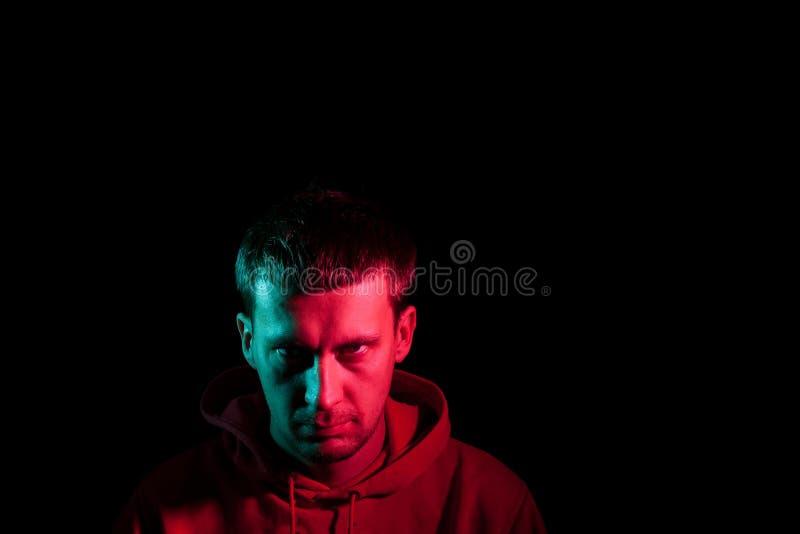 Nära övre stående av framsidan av en vuxen allvarlig manblick frowningly: rak näsa, uttrycksfulla ögon, öron, skägg; upplyst arkivbilder