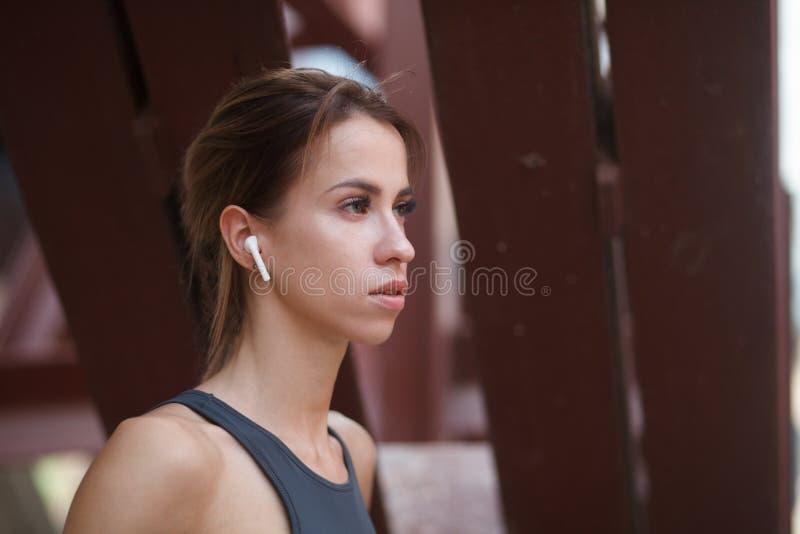 Nära övre stående av konditionkvinnan med den trådlösa headphonen arkivbilder