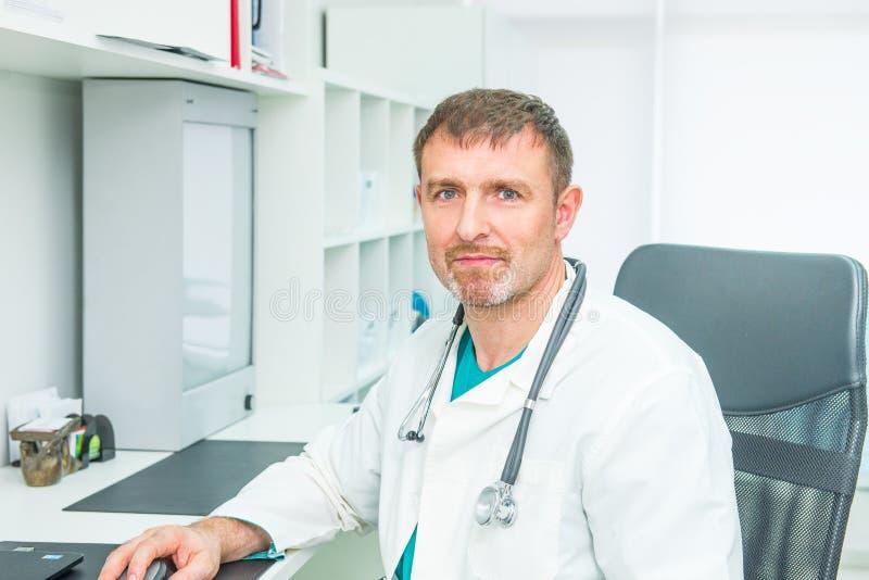 Nära övre stående av manlig mogen doktorskänsla som är säker i honom, medan sitta på hans arbetsplats och se kameran royaltyfri bild