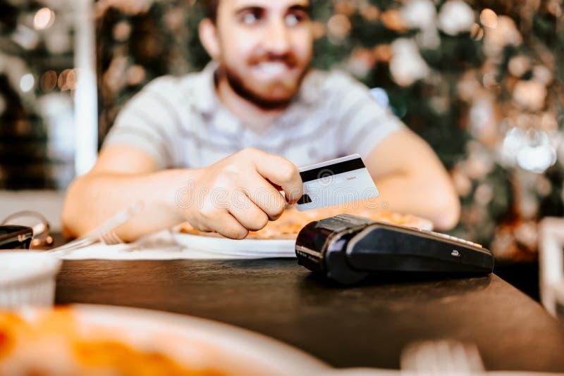 Nära övre stående av mannen som betalar med kreditkorten på restaurangen Fokus på händer, kort och betalningterminalen arkivfoto