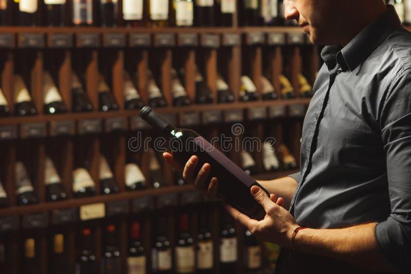 Nära övre stående av sommelieren som rymmer vinflaskan på bakgrund för vinkällare arkivbild
