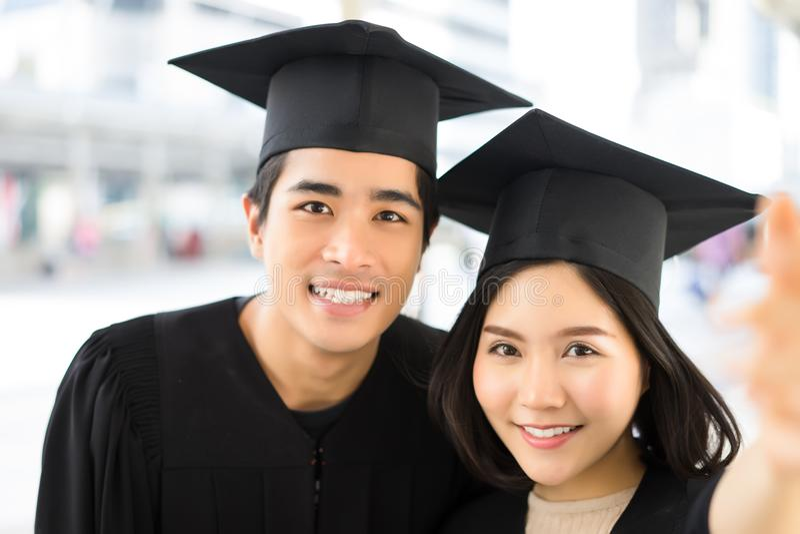 Nära övre stående av två lyckliga avlägga examen studenter som använder ett smart royaltyfri bild