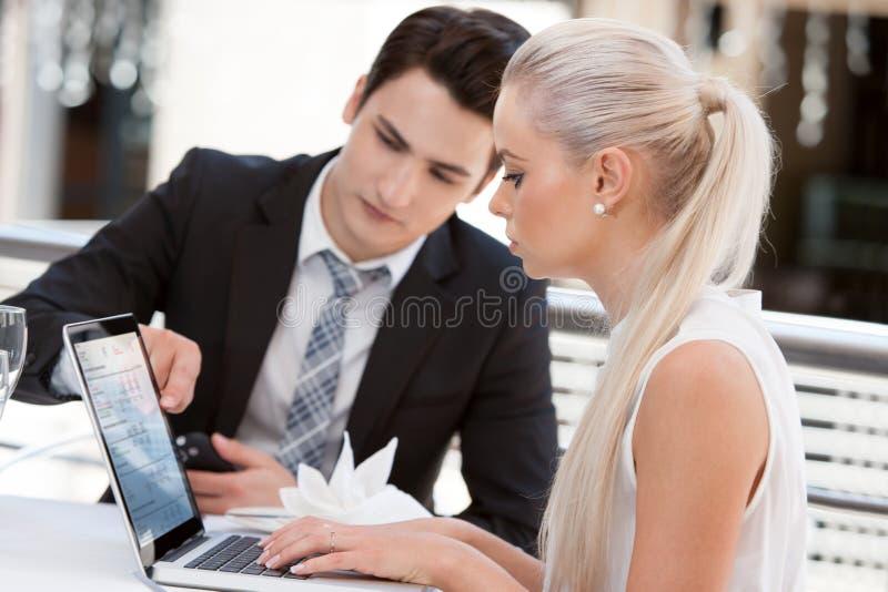 Affärspartners som granskar arbete på lunch. arkivbilder