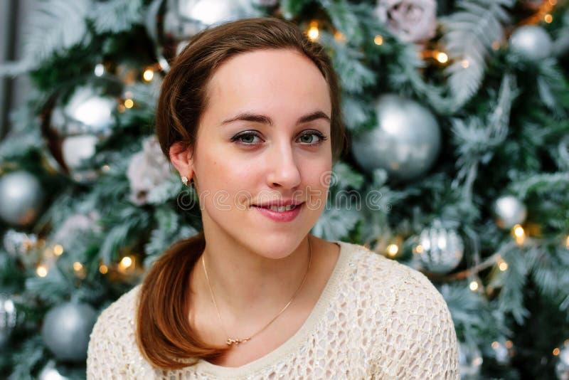 Nära övre stående av unga flickan bak julträd royaltyfri fotografi