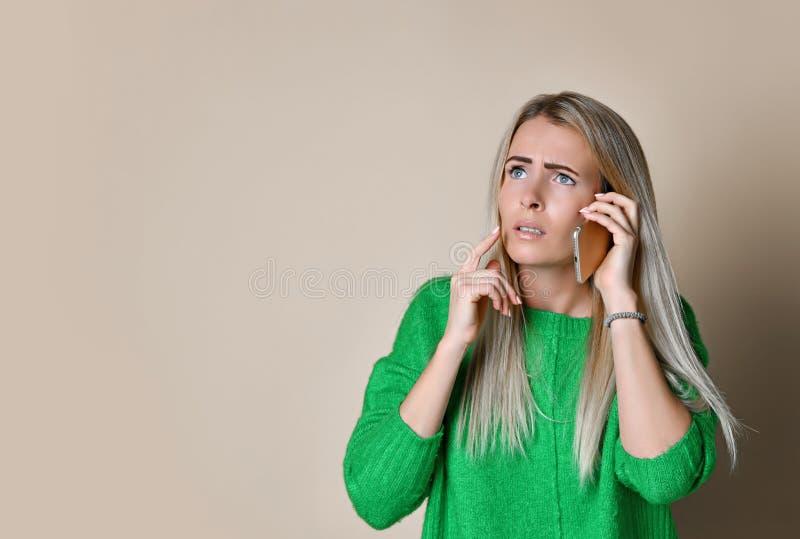 Nära övre stående av unga flickan i grön tröjablick åt sidan och att tala på den moderna digitala grejtelefonen på ljus bakgrund arkivbilder