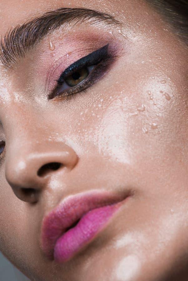 Nära övre stående för gamourskönhetkvinna Dana våt skinande hud, med för glanskanter för droppar sexigt smink och rosa ögonbryn arkivbilder