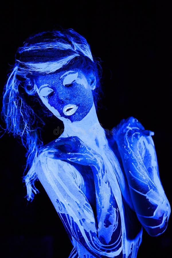 Nära övre ståendeung flicka som målas i ultraviolett målarfärg arkivfoton