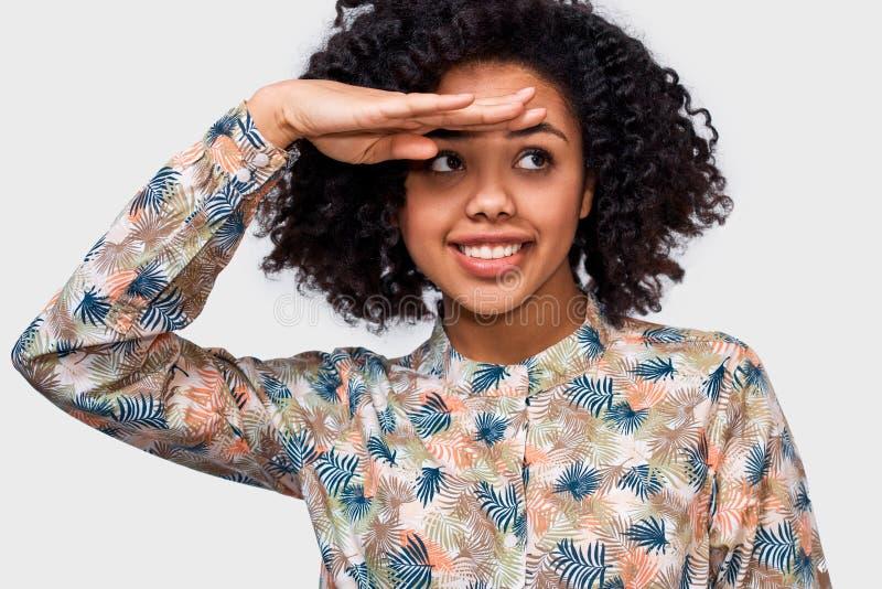 Nära övre studiostående av den unga kvinnan för härlig afrikansk amerikan som bort ser med handen på pannan som i huvudsak ler royaltyfri foto