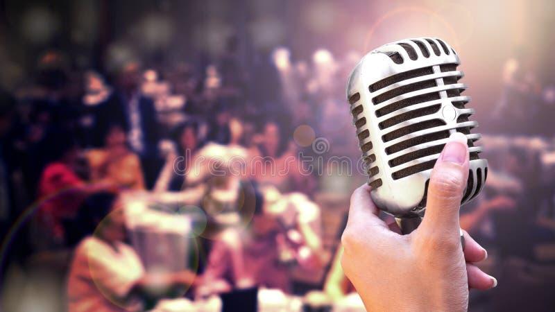 Nära övre tappningmikrofon i sångarehanden som sjunger på etapp av att gifta sig händelsepartiet eller affärsmöte med belysningef arkivfoto