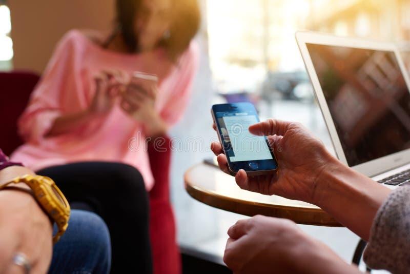 Nära av den unga personen använder mobiltelefonen för information om sökande under vilar i kafé arkivbild