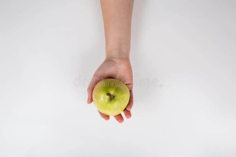 Nära en mänsklig hand som håller ett färskt päron isolerat på vit bakgrund med kopieringsutrymme Biohaltiga frukter Hälsosam orga royaltyfri foto