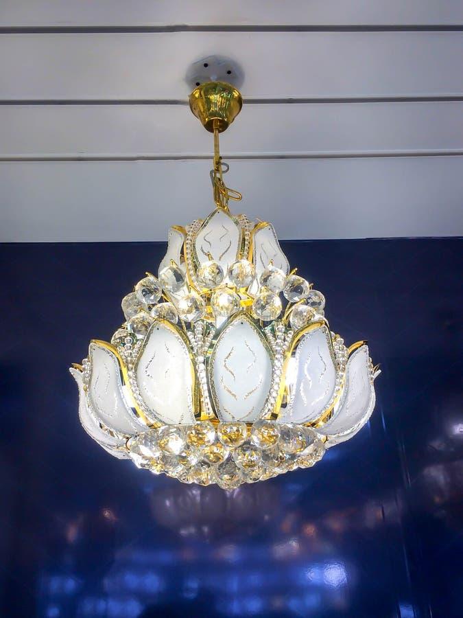 Nära en vacker, kristallklar, ljuvlig ljuskran dyrbara råjärn som hänger under taket royaltyfri foto