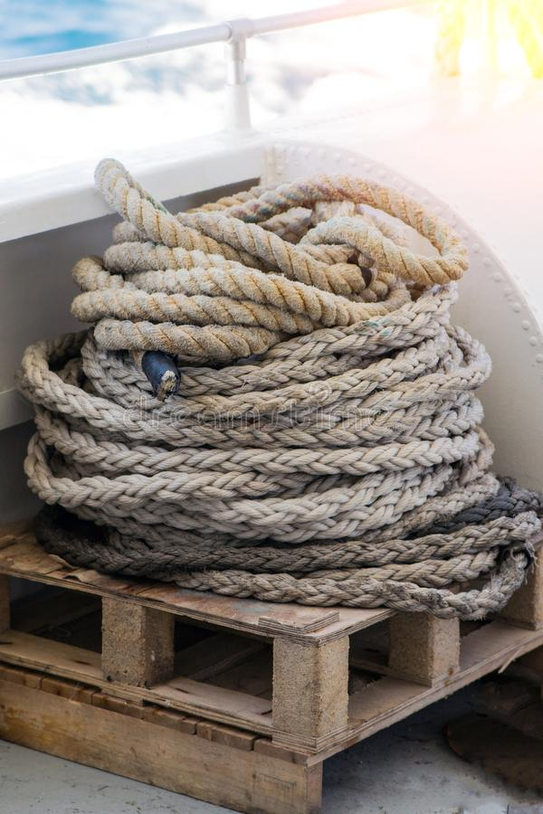 Nära ett förtöjningslinje med en knuten ände som är bunden runt en knivstift på ett trästrå förtöjning av nautisk repor arkivbild